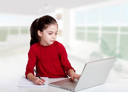 little girl studyng with computer