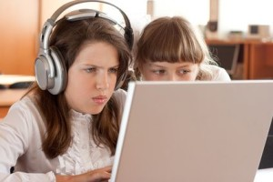 Two schoolgirls concentrated on their task with notebook