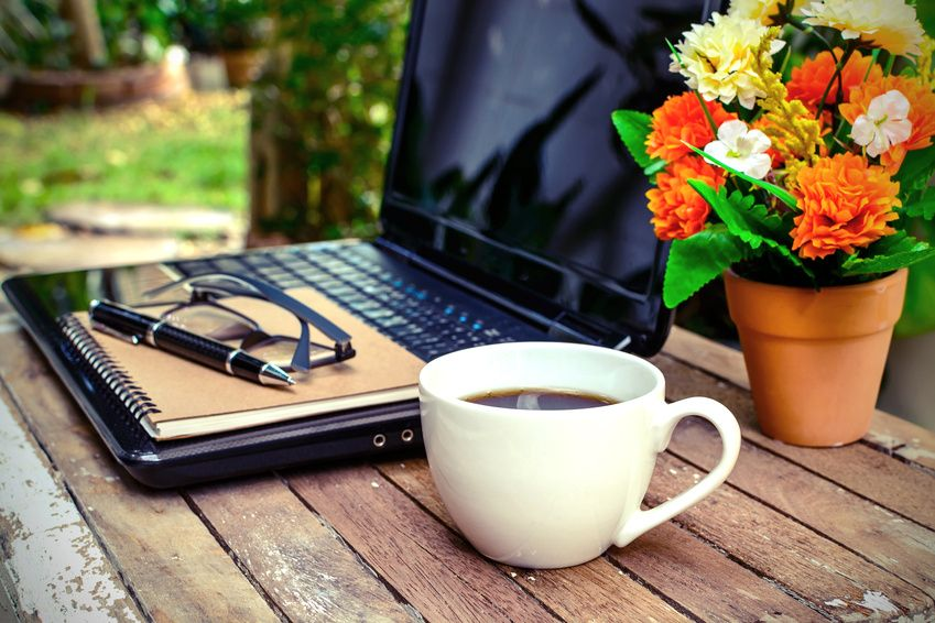 cup of coffee and laptop on wooden table with flower and notebook in the garden, Vintage style